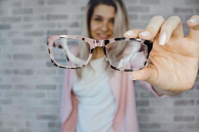 Kobieta trzymająca okulary