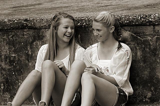 Dwie koleżanki siedzą i się śmieją